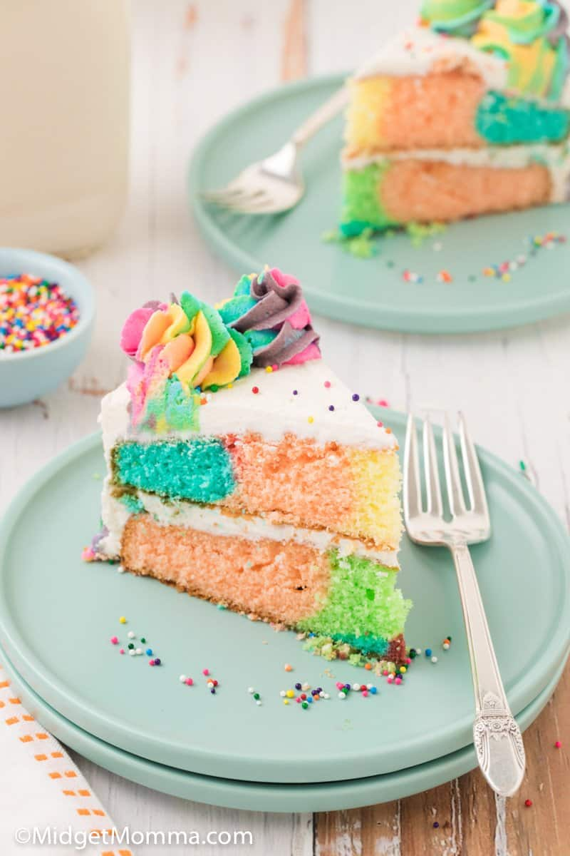 slice of rainbow cake on a plate with a fork