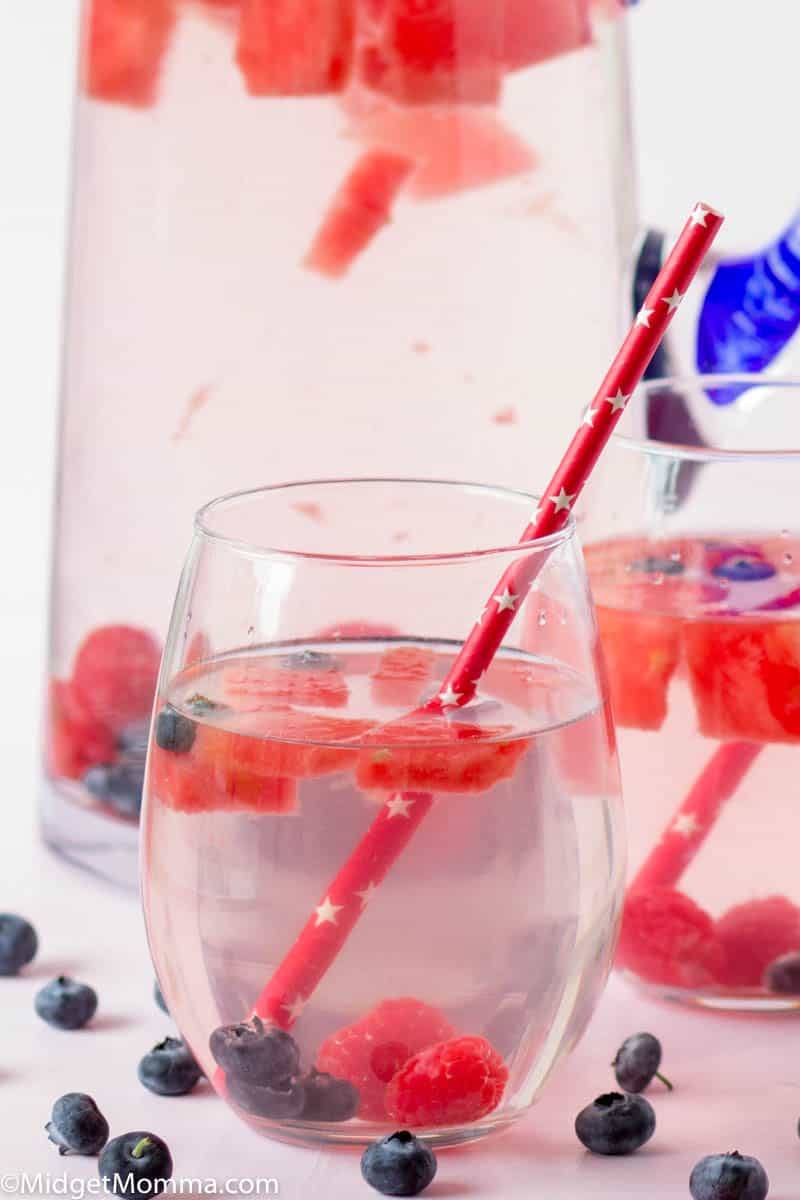 Fruit Infused water with raspberries, blueberries and raspberries in a glass pitcher with a glass of water poured next to it