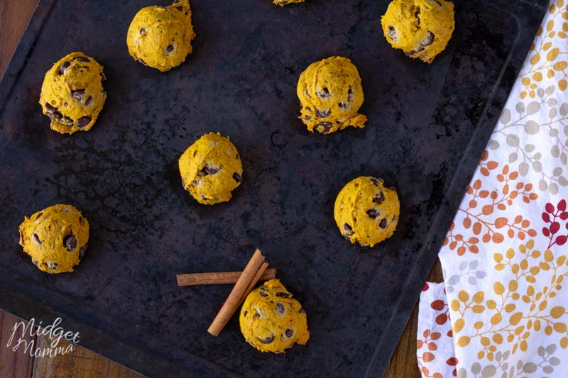 8 easy pumpkin chocolate chip cookies on a baking sheet with fall cloth napkin and cinnamon sticks