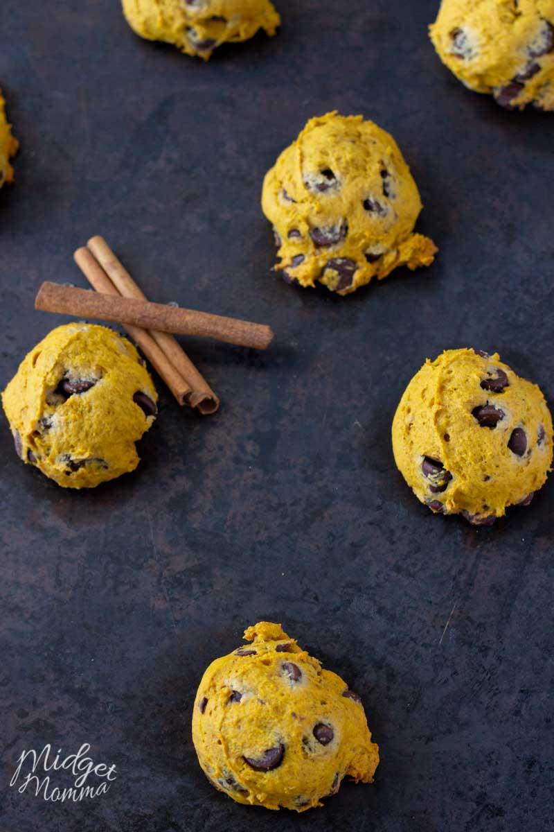 4 pumpkin chocolate chip cookies on a baking sheet