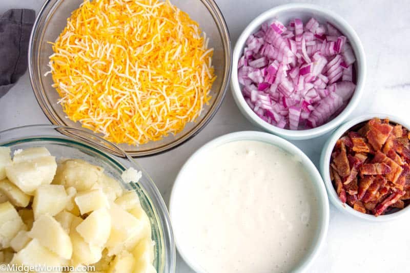 Loaded Bacon Ranch Potato Salad ingredients- bowls with potatoes, ranch dressing, red onion, bacon and cheese