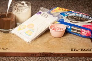 Silmat baking mat with all the ingredients to make chocolate covered oreo pops. Oreo cookies, crushed peppermint candy canes in a bowl, a bowl of melted milk chocolate and a bowl of melted white chocolate and a package of lolipop sticks