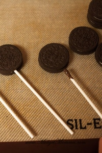 Undipped chocolate oreos on a silicon mat with lolipop sticks in them