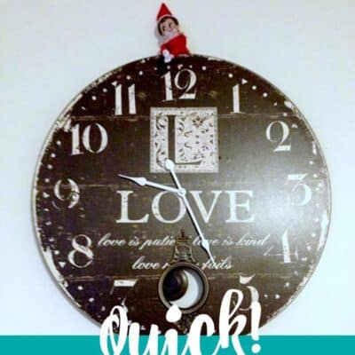 Elf on the shelf hanging from a clock