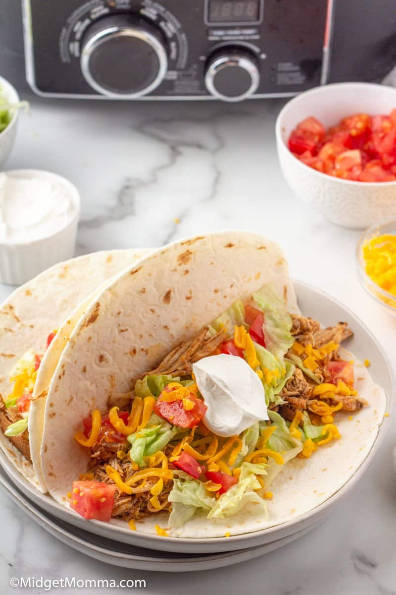 Open chicken taco in soft taco shell with lettuce, tomato, cheese and sour cream
