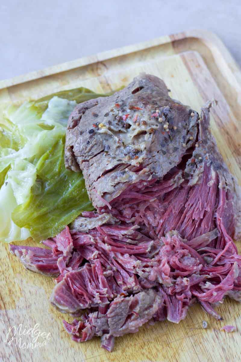 Sliced corned beef and cabbage on a cutting board.