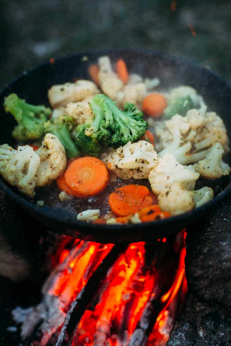 Cauliflower, broccoli and carrot in a pan. Cooking on an open fire. Outdoor food. Grilled vegetables. Food on a camping trip