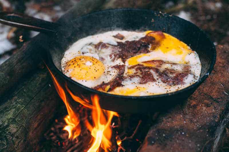 Fried eggs with bacon in a pan in the forest. Food at the camp. Fried egg with bacon on fire. Picnic