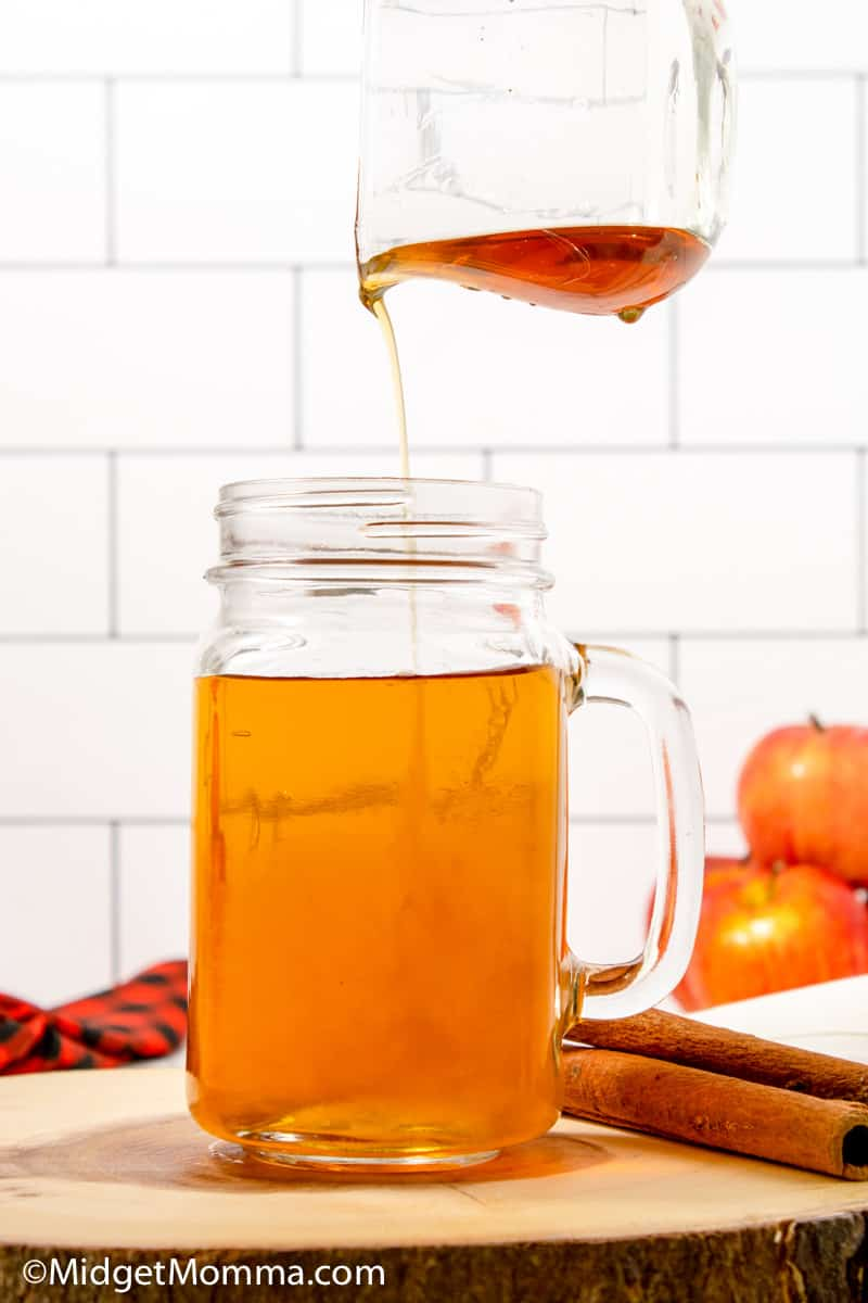 cinnamon dolce syrup being poured into a glass of apple juice