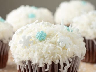 Disney Frozen Inspired Snowball Cupcakes are chocolate cupcake coated in coconut and snow flake sprinkles. Any snowman would love these.