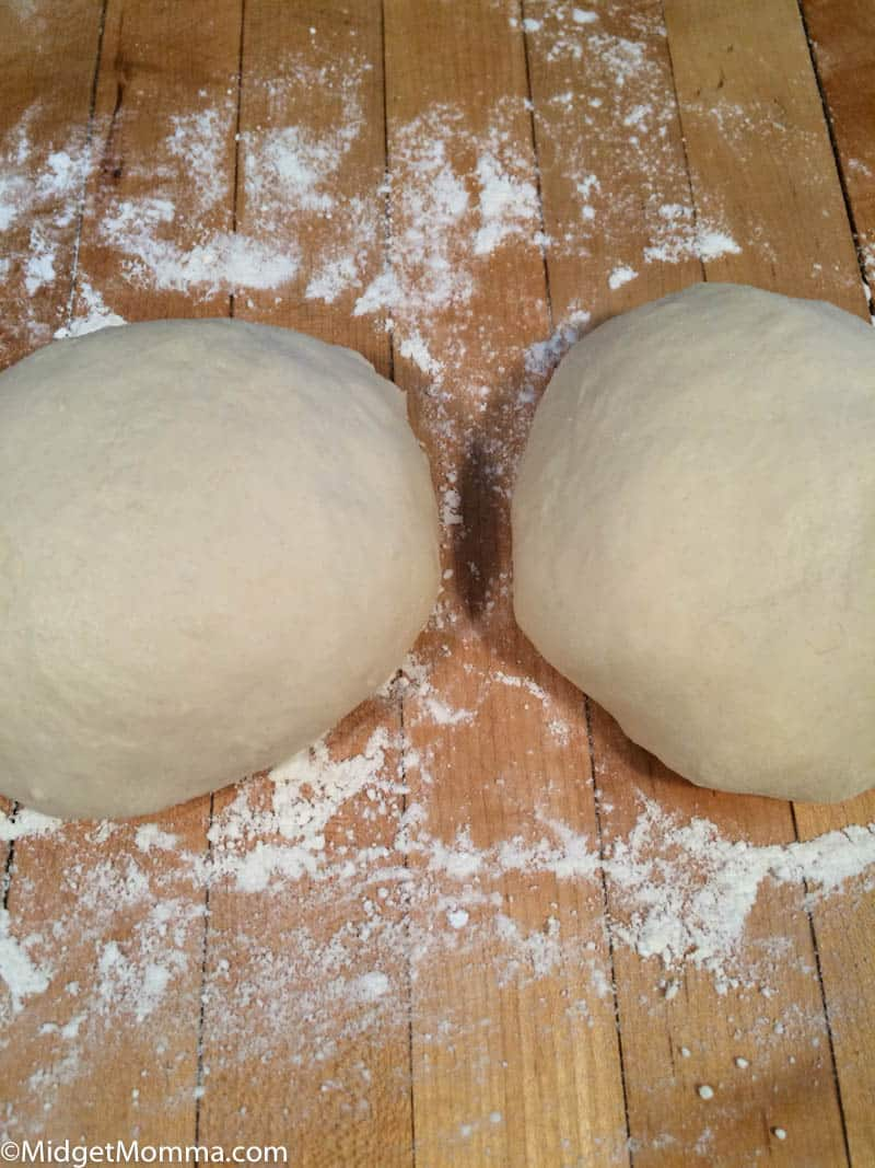 2 balls of pizza dough on a floured cutting board