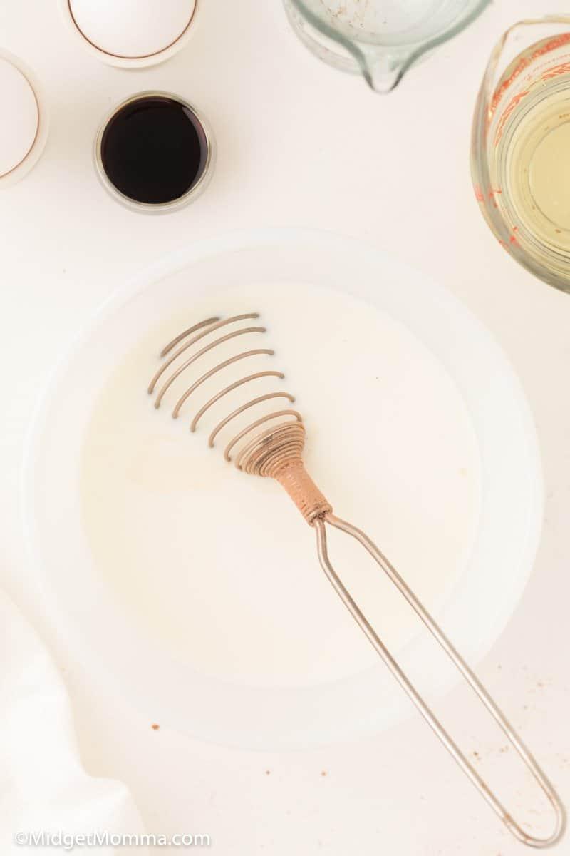 eggs, whole milk, oil, and vanilla ini a bowl