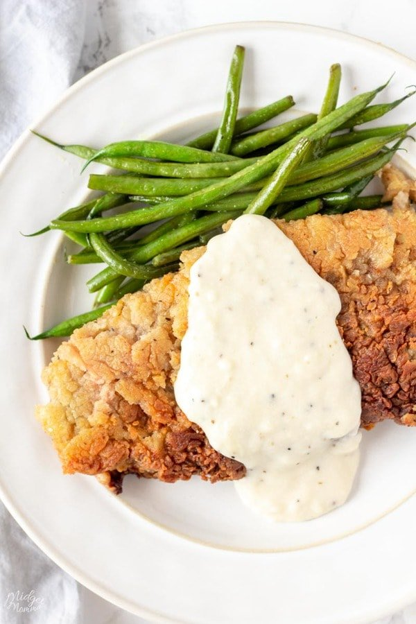 Chicken Fried Steak covered with white gravy on a white plate with green beans
