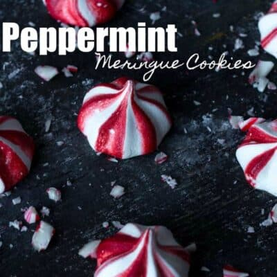 A few of fresh made peppermint meringue cookies on a black baking sheet