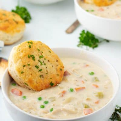 Chicken Pot Pie Soup in a bowl with a biscuit