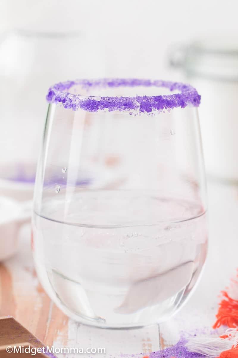purple colored sugar on the rim of a glass