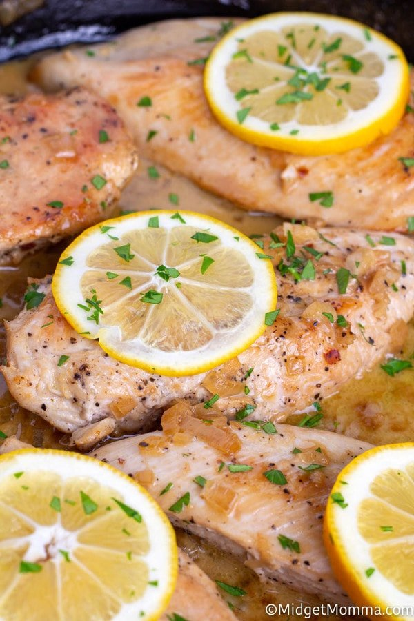 Close up of cooked baked lemon garlic chicken in a skillet
