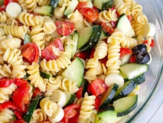 Easy Italian Pasta Salad in a bowl with rotini noodles, cucumbers, olives, tomatoes and italian dressing