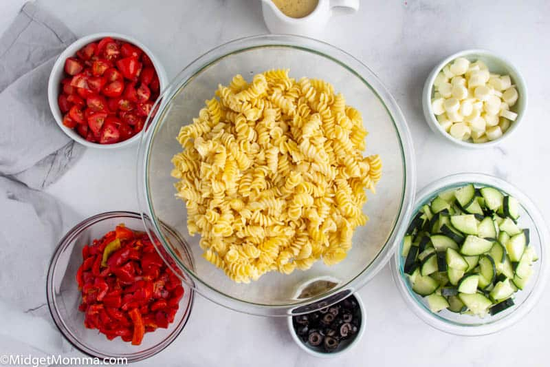 Italian Pasta Salad ingredients in bowls with cooked pasta noodles