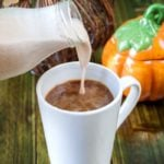 homemade pumpkin spice creamer being poured into a cup of coffee
