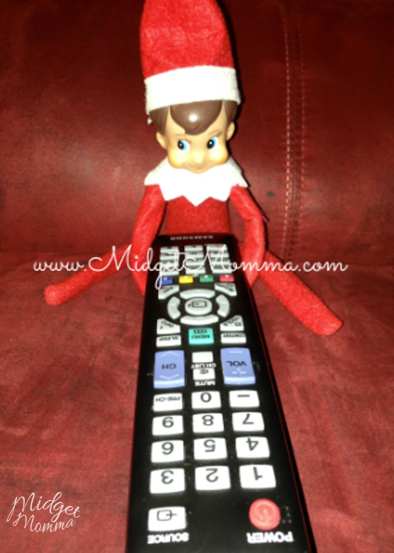 Easy Elf on the Shelf Ideas- the elf steals the remote and is sitting on the couch