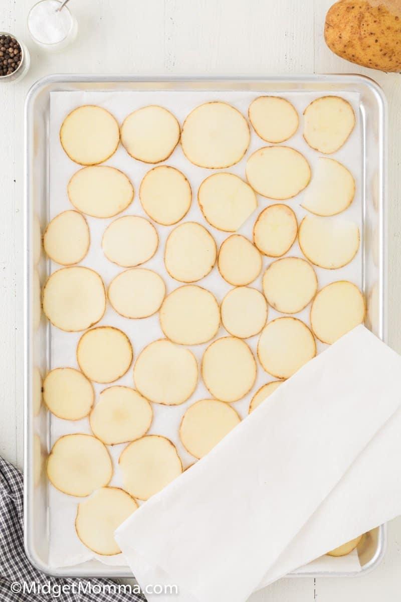 sliced potatoes drying on a baking sheet