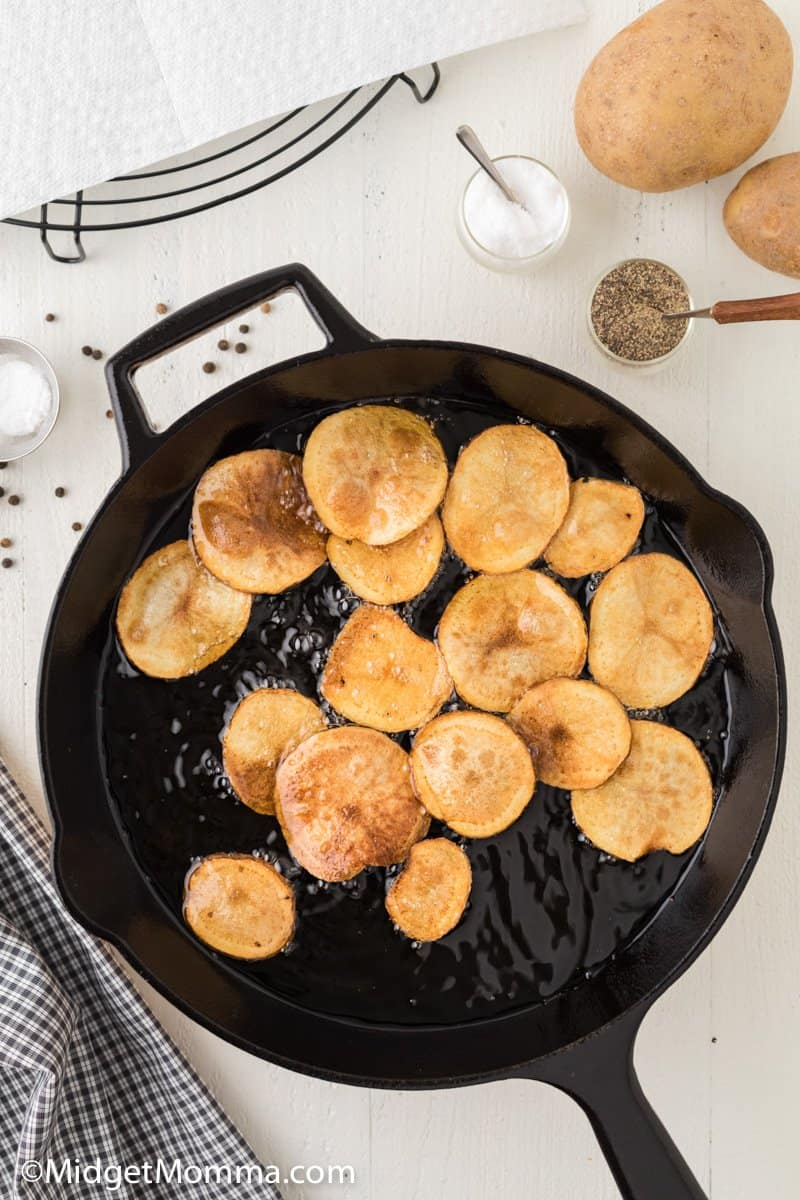 potato chips cooking in a cast iron skillet
