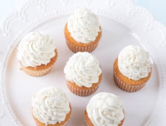 the best vanilla cupcakes topped with vanilla buttercream on a white platter