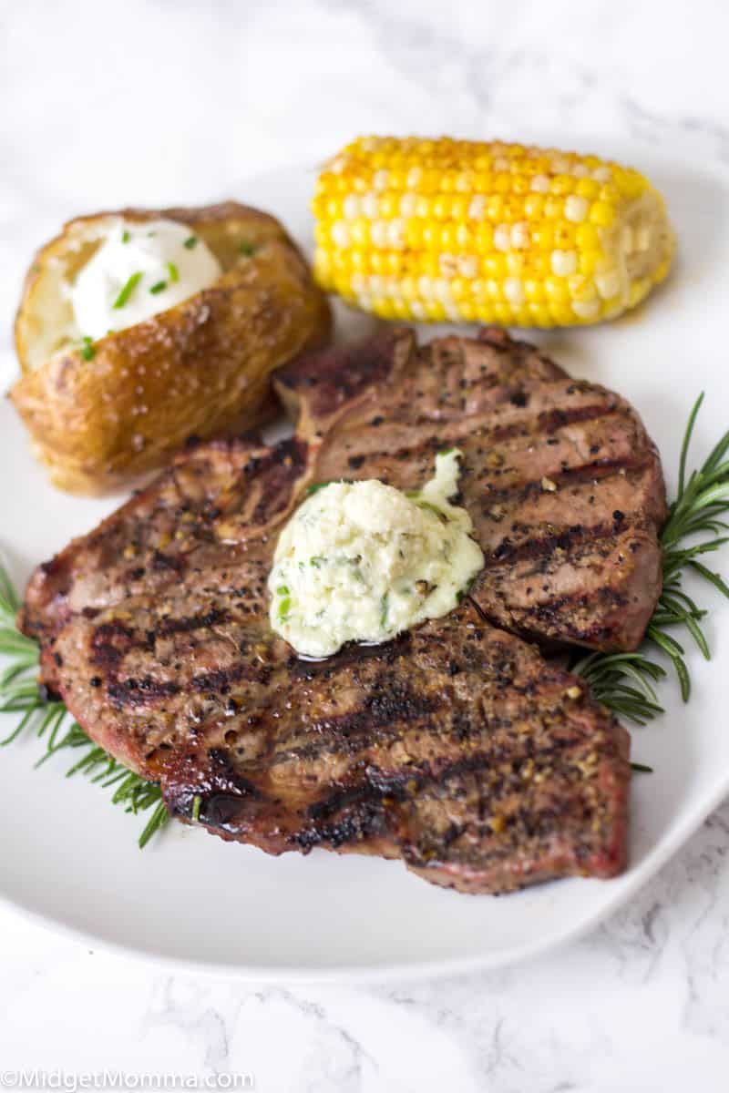 Grilled steak with a baked potato and corn on the cob on a white plate