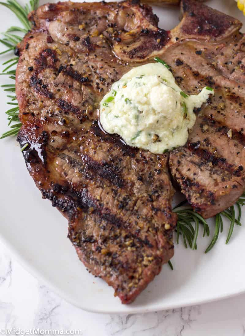 Grilled Steak on a white plate topped with blue cheese butter