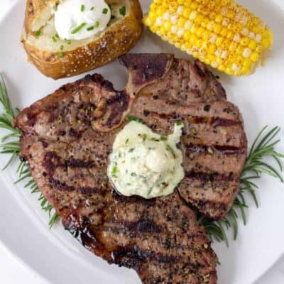 Grilled Steak on a white plate topped with blue cheese butter compound