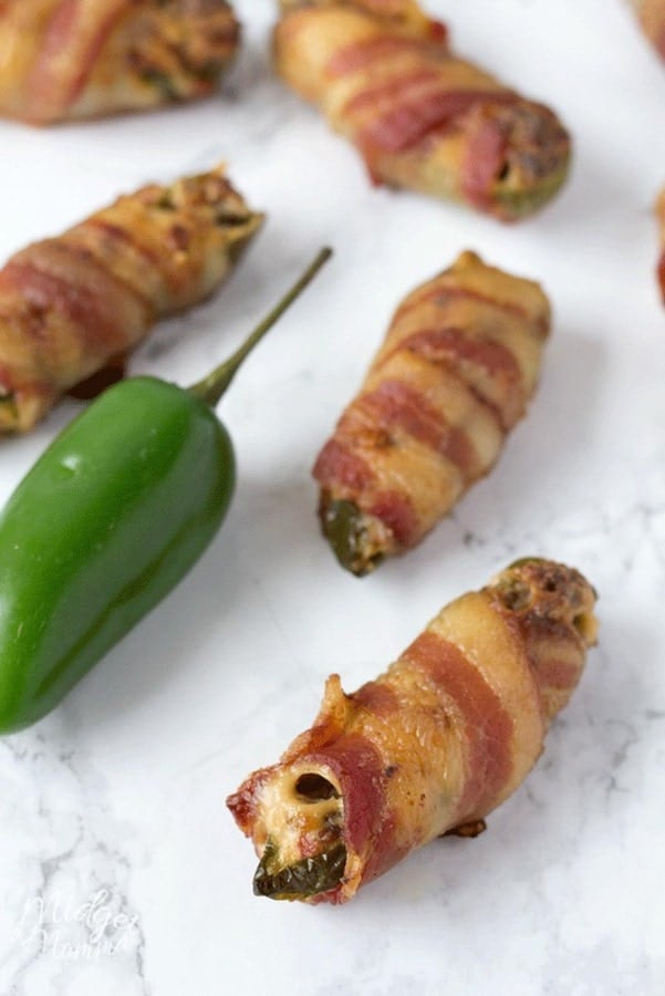 Jalapenos poppers stuffed with cream cheese and sausage wrapped in bacon