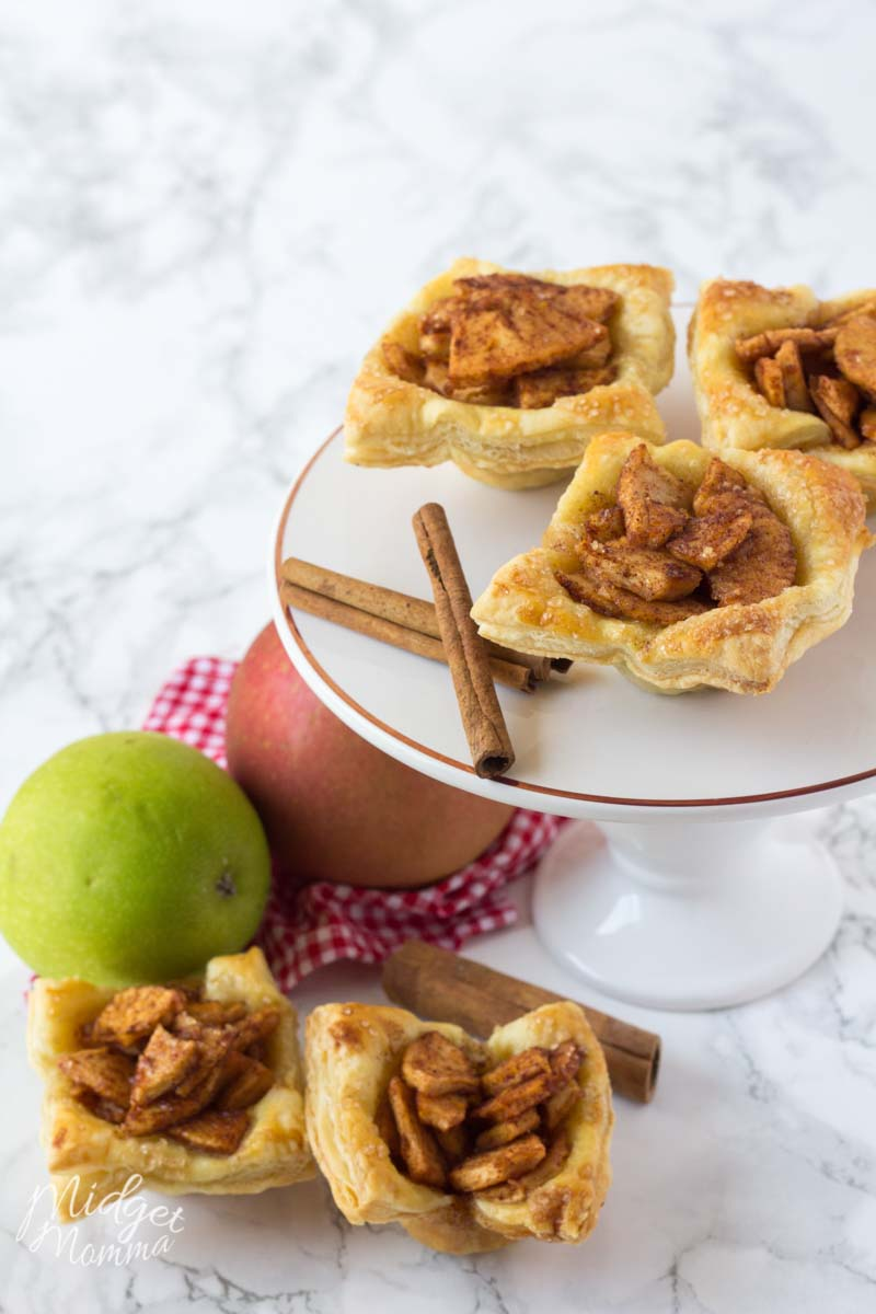 apple puff pastry - 3 set on a cake pan and 2 next to it in the perfect apple pie dessert display