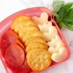 pizza crackers in a lunch box with mozzarella cheese, pepperoni and crackers