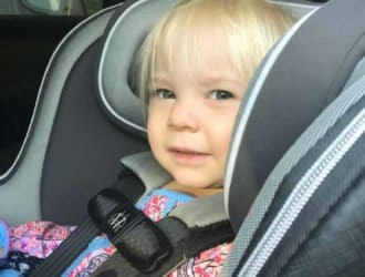 smiling and Happy child sitting rear facing in their car seat