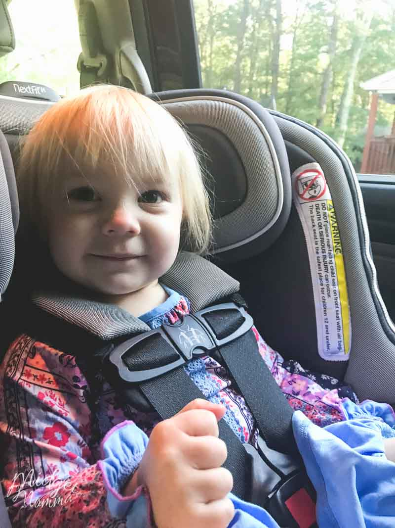 Child smiling and happy while sitting rear facing in the car age 2