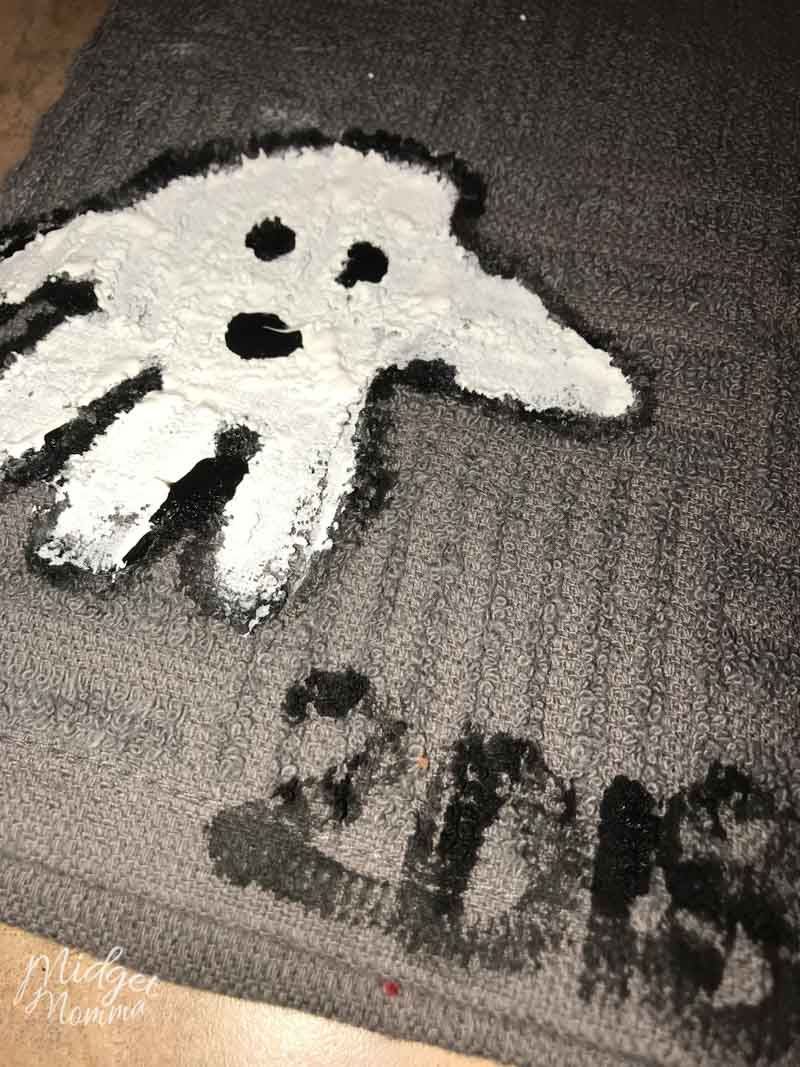 Halloween ghost handprint towel. Grey towel with kids hand print in white paint and black paint to make the eyes and mouth.