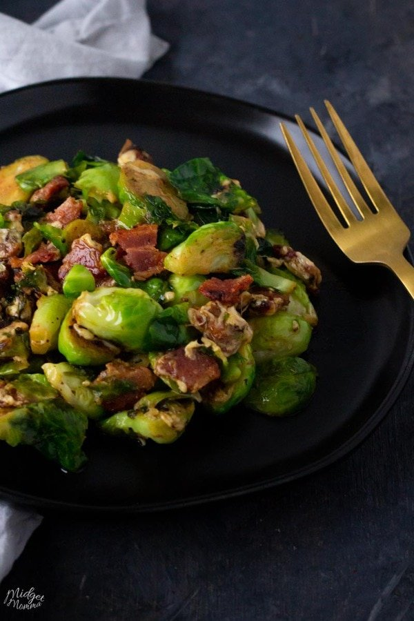 Cheesy Brussel Sprouts with bacon on a black plate