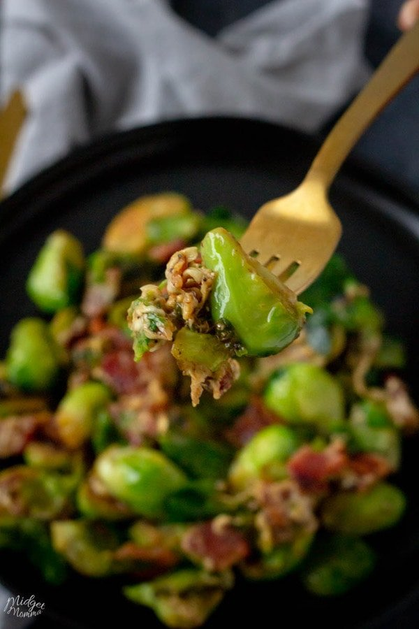 Brussel sprouts with bacon side dish recipe on a black plate, with a fork full of cheesy brussel sprouts
