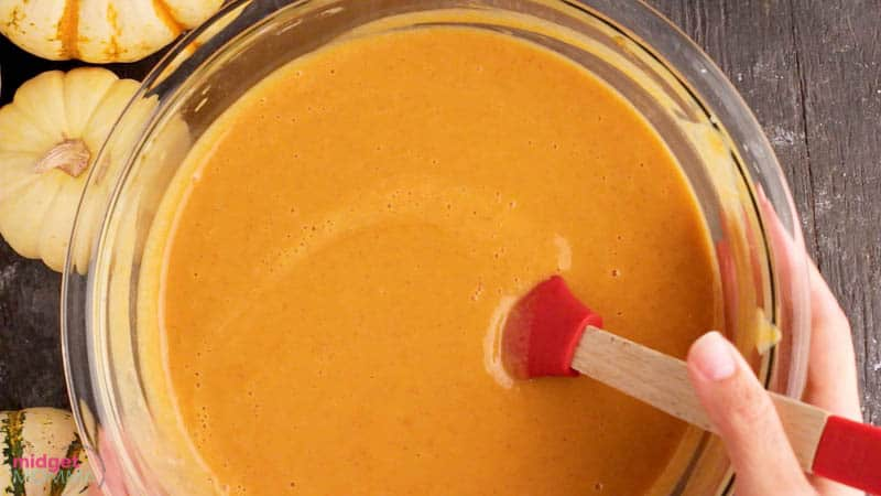 evaporated milk being mixed with pumpkin puree and granulated sugar, salt, ginger, cloves and cinnamon