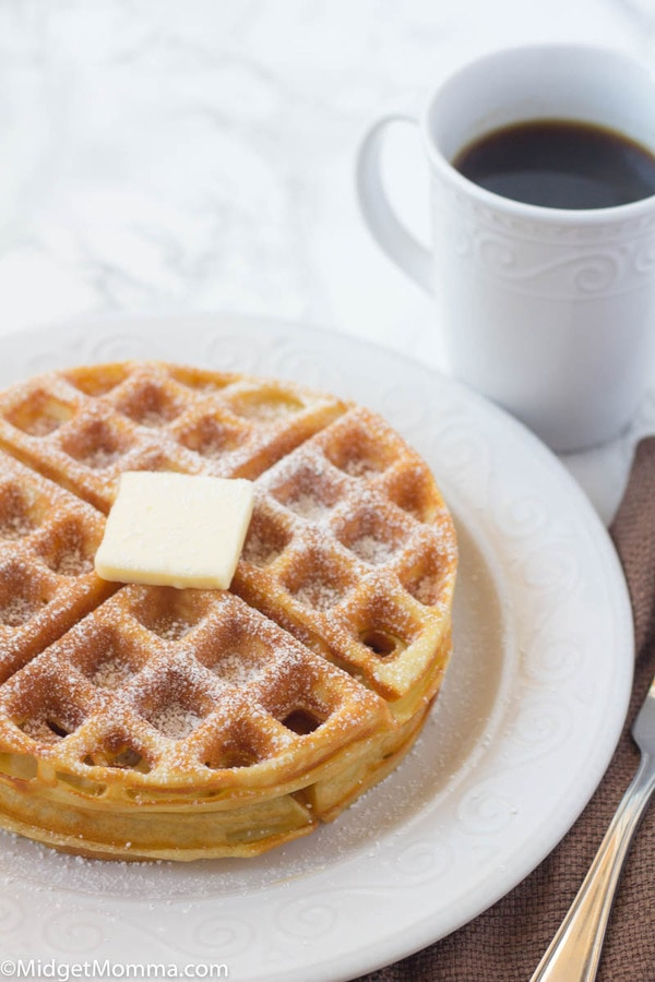 Easy Belgian Waffles Recipe stacked on a plate with butter and a cup of coffee