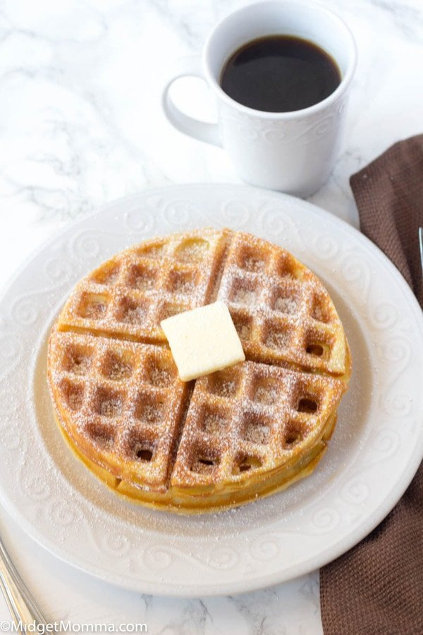 How to Make Belgian Waffles Recipe - 2 belgian waffles on a white plate topped with powdered sugar and butter