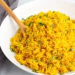 Instant Pot Turmeric Rice in a white bowl with a wooden spoon