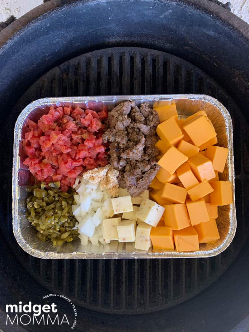 Smoked Queso Dip ingredients in a pan on the grill