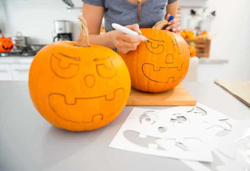 Close up on woman creating pumpkins Jack-O-Lantern for Halloween party in kitchen. Traditional autumn holiday