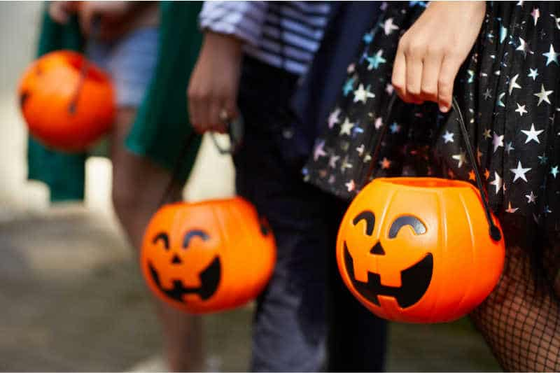 Close-up of children with pumpkins bags playing trick or treat outdoors