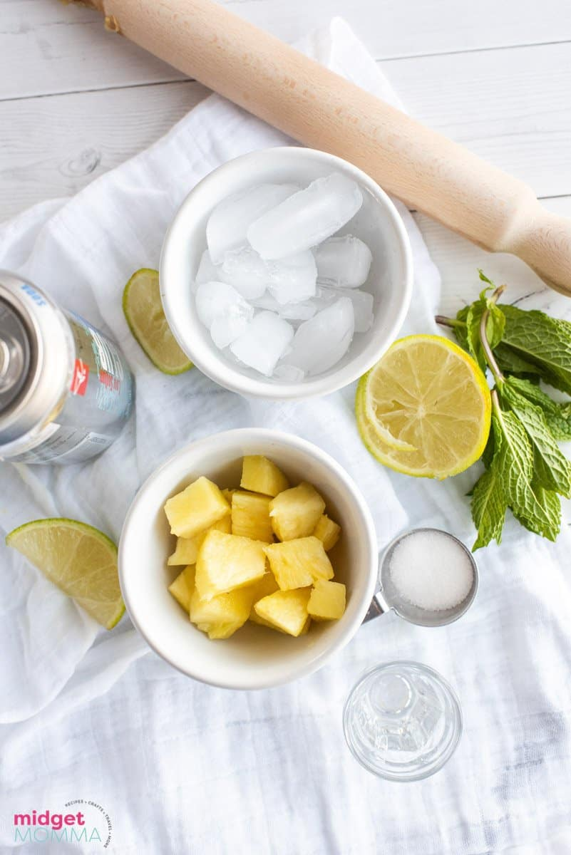 pineapple mojito ingredients -bowl with pineapple, bowl with ice, mint leave, lemon, lime and rum