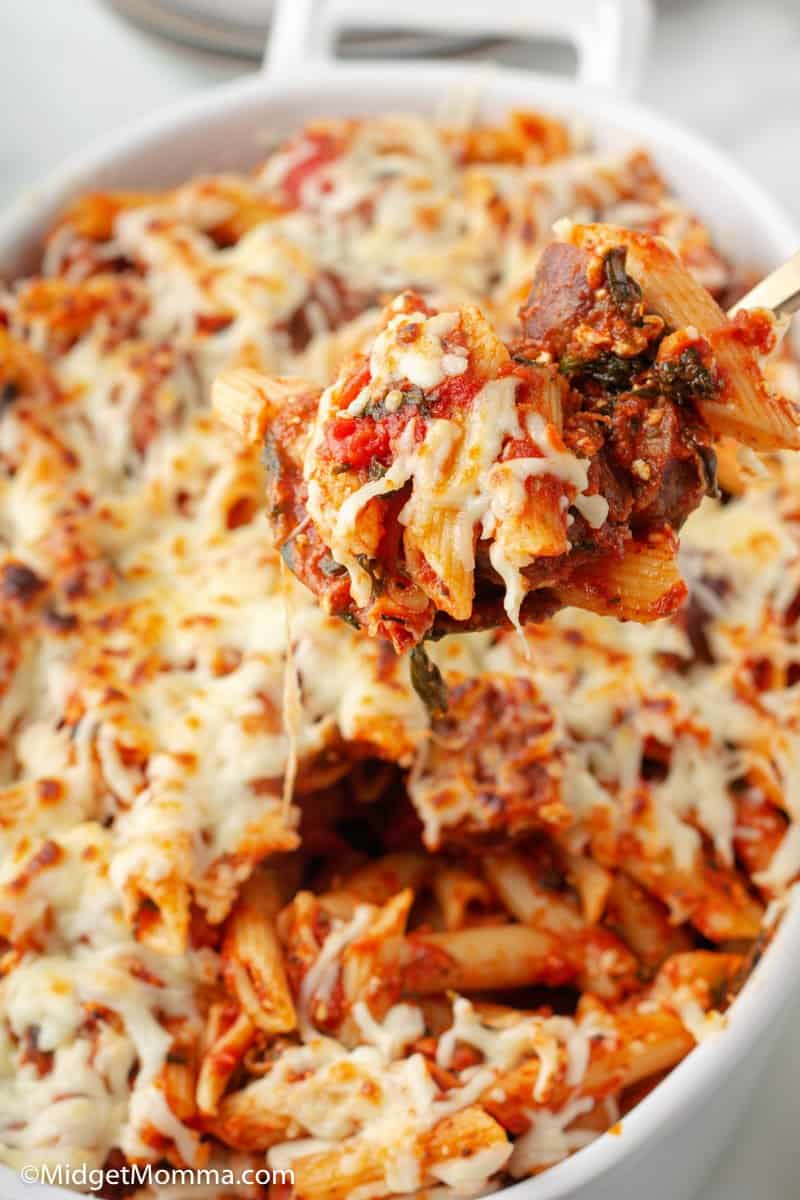 baked penne pasta being schooped with a spoon out of the dish