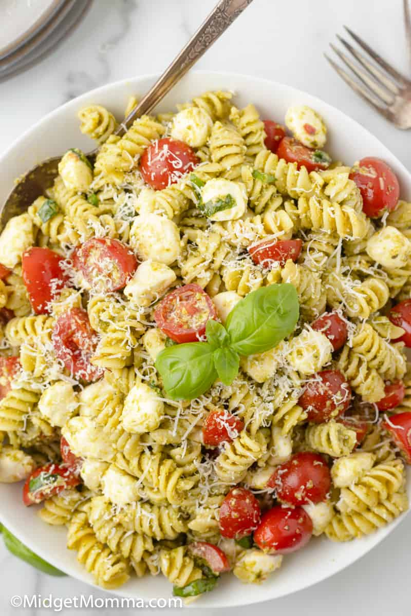 over head photo of pesto pasta salad in a bowl with a serving spoon